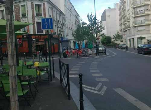 "This photo is one example of Paris' ""complete street"" strategy. It's a one-way street (previously two lanes), reduced to one lane, with more pedestrian area plus a bike lane that allows cycling against the traffic"