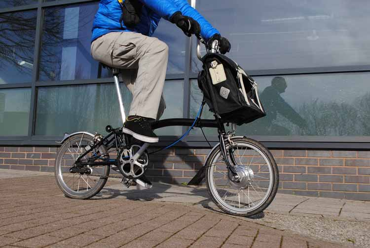 Sparticle converts Bromptons to e-bikes by way of a battery in the front bag.